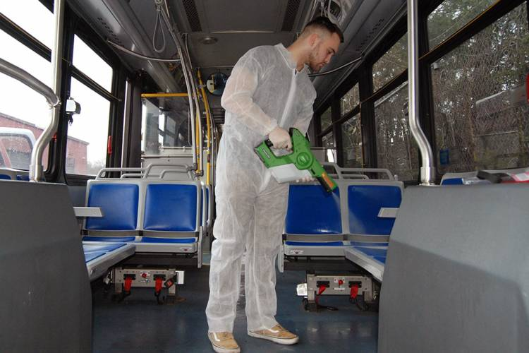 A worker sanitizing a bus at Duke