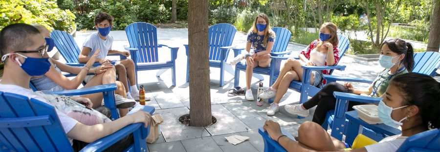 Duke students sitting in a large circle of adirondack chairs